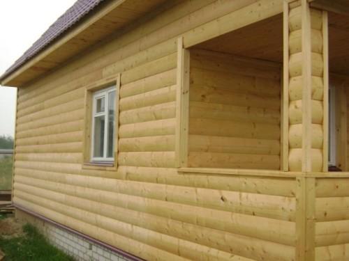 На фото - стена дома, обшитого деревянным блок хаусом