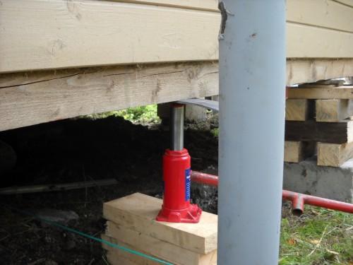 Поднятый домкратом сруб деревянного дома